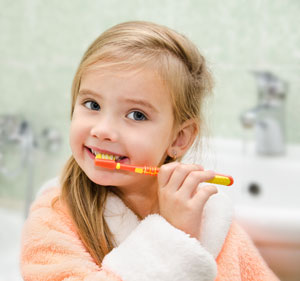 Girl Brushing Teeth with Toothpaste - Pediatric Dentist Serving Houston, Memorial and The Heights, TX